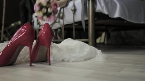 nevěsta leží na posteli a hází kytici na podlaze. První svatební noc. boty detail Zenske a svatební kytice na podlaze