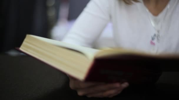 Cute young woman reading book. Close-up of book binding