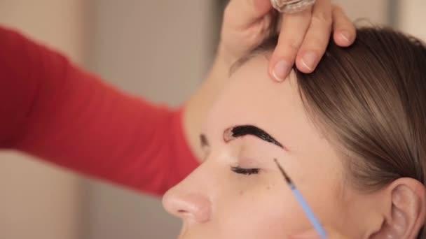 Professionelle Visagistin zeichnet Augenbrauen der Kundin mit Henna
