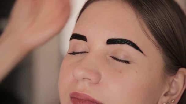 Profesionální vizážistka kresba obočí klienta s hennou