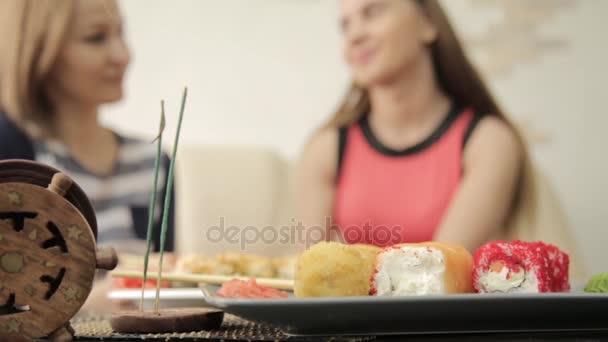 dvě kamarádky krmit navzájem během večeře v restauraci, s hůlkami jíst rohlíky