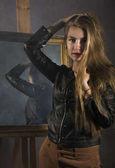 schöne junge Frau in Lederjacke posiert auf einem Spiegelhintergrund