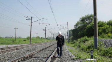 Inspector of railway traffic irritably talking on walkie-talkie. Railway worker in white helmet walking along the railway