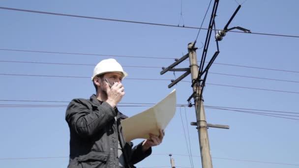 Technik kontroly elektrických systémů mluvit vysílačku, inspektor drží plán plánování