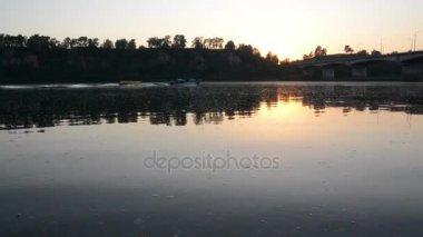 Naplemente a folyón, a hajó vitorlák, a folyó mentén