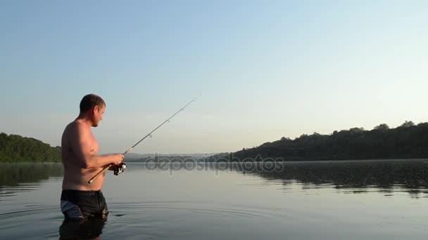 rybář loví v klidné řeky ráno. Muž v stending gear rybaření v řece a vyvolá rybářský prut