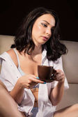 Photo Sexy woman in a white mans shirt sitting on a leather sofa and holding cup of coffee on a dark background