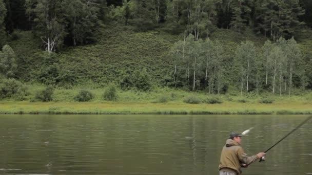 Örömteli Halász halászat, nyugodt folyó víz, a part közelében