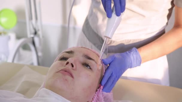 beautician doing facial skin care with electric darsonval. Cosmetic procedure