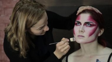 Make-up artist applying make-up to model. Attractive model girl with Halloween make-up