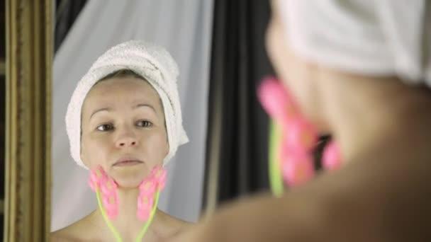 krásná žena v ručníku dělá kosmetických procedur v domácnosti. masáž obličeje s masážní