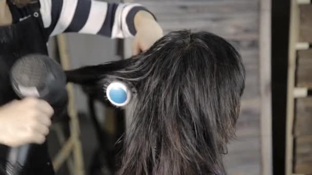 Profesionální kadeřník dělá vlasový styling pro krásné ženy klienta a použít fén na vlasy s hřebenem