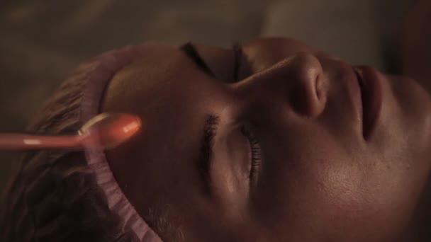 Beautiful woman has a electric darsonval massage procedure in a dark