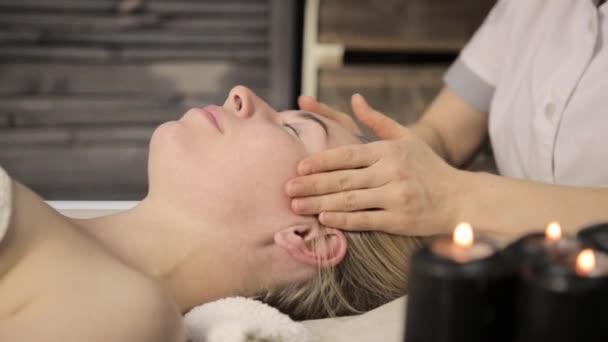 Krásná žena dostává masáž obličeje. Finger masáž s olejem na beauty Spa.