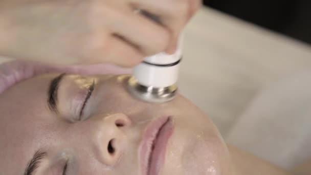 Hochfrequenzbehandlung. Kosmetikerin macht RF-Lifting für eine Frau im Schönheitssalon.