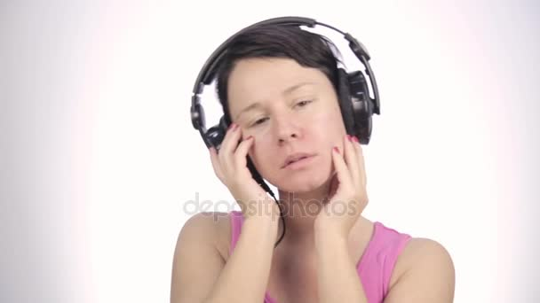 brunette woman listening music with big headphones and dancing on a light background