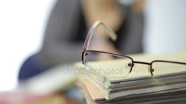 szemüveg egy halom füzet, nő dolgozik szemüveg nélkül látás korrekció után