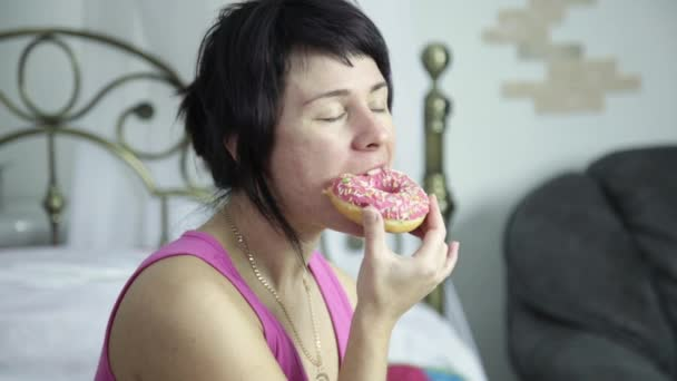 woman eating a donut on a bed, breakfast with junk food