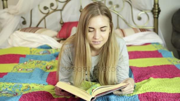 Krásná mladá žena s knihou na posteli doma. domácí učení