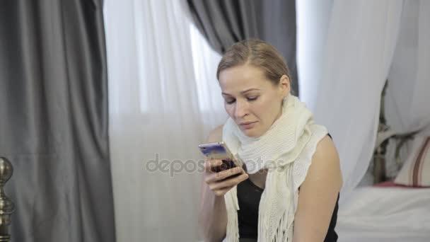 Smutné, emocionální žena pláče a odešle zprávu na mobilní telefon