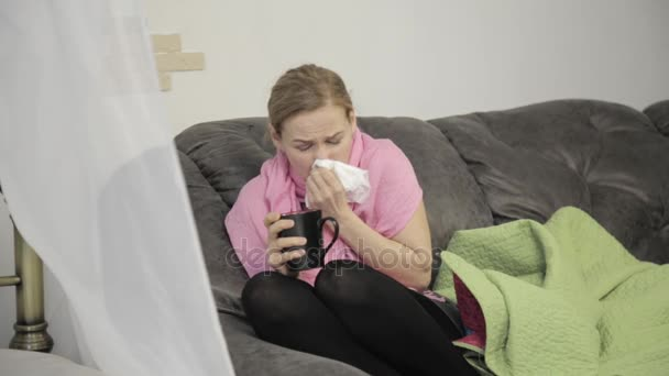sick woman wipes his nose using a napkin and sheltered by a warm blanke