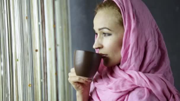 krásná muslimská Arabská žena v růžové hidžáb pije cofee přední okna