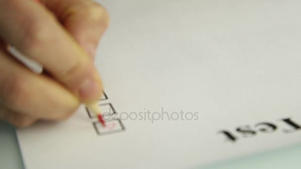 close-up hand of student filling out answer sheets with red pencil