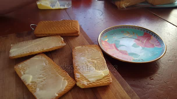 Spreading butter on a wheat cracker for breakfast with a knife