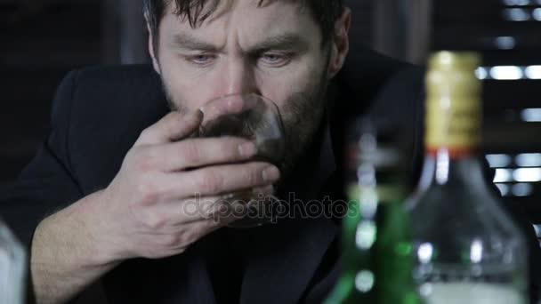 részeg ember iszik alkoholt, sok körülötte üres palackok