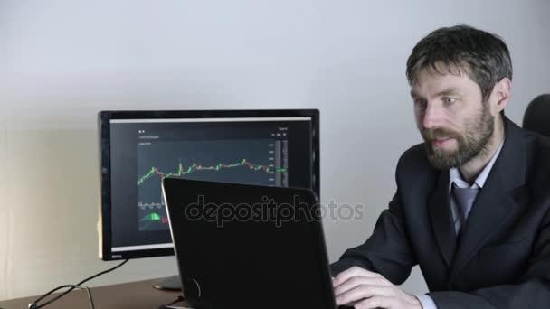 kereskedő figyeli a változásokat a valuta átváltási diagram, látszó-on laptop. A tőzsdén dolgozik.