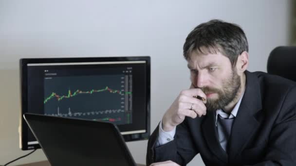 trader watching changes in the currency exchange chart, looking at laptop. Work on a stock exchange.