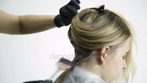 Stylista platí vlasy obarvení na vlasy žena v beauty studio