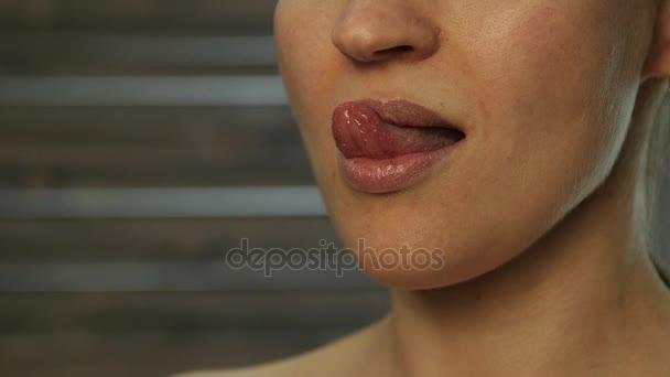 Forró szőke lány nyalogatja a száját. nyelv munka. lassú mozgás