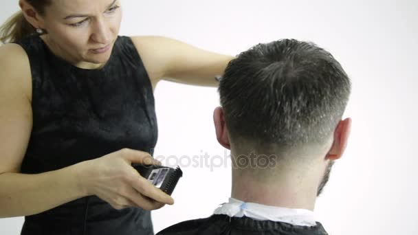 Female hairdresser shaping mens hair cutting uses scissors in a beauty saloon