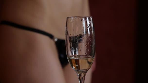 Die schöne junge Frau im Mini-Bikini gießt im Dunkeln Champagner in Gläser. Nahaufnahme von Gesäß und Hüfte