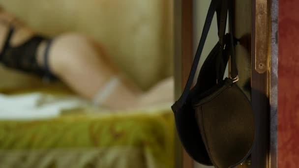podprsenka na klice, blured sexy žena v punčochy a prádlo na posteli v hotelovém pokoji