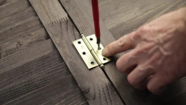 Arbeitskraft ist das Türscharnier bis ins Möbel mit Schraubendreher befestigen.