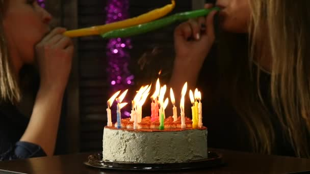 dvě šťastné emocionální žena sfoukl svíčky na narozeninový dort, svíčky uhašen. Zpomalený pohyb