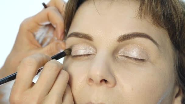 Oční make-up žena použití eyeshadow prášek. Stylista dělá make up pro ženy tužka na oči