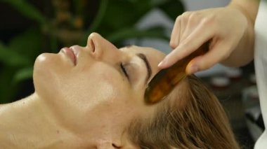 beautician does facial massage for beautiful woman in spa saloon. 4K