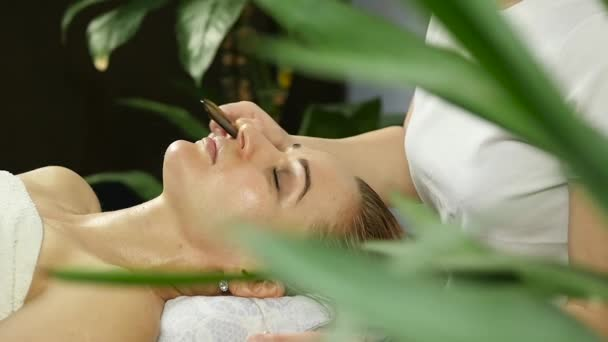 Schöne Frau immer Gesichtsmassage im Spa. Gesichtspflege im Beauty-Salon. zeitlupe