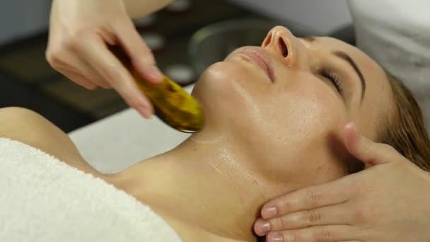 schöne Frau bekommt Gesichtsmassage im Wellnessbereich. Gesichtspflege im Schönheitssalon. Zeitlupe