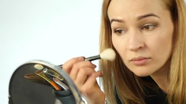 Krásná žena dělá každodenní make-up a drží make-up štětce v přední části zrcadlo. Zpomalený pohyb