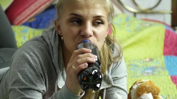 Zufriedene Frau isst Fast-Food-Burger mit einem sprudelnden Getränk auf einem Bett in ihrem Zimmer. sehr Junk Food. Zeitlupe