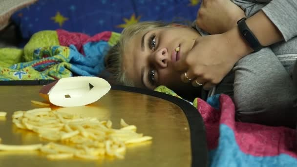 Woman eating junk food with great enjoyment. girl eats french fries. slow motion