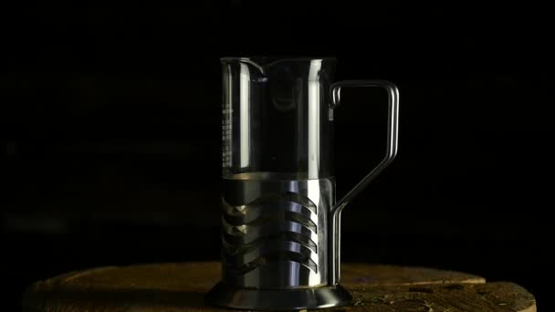 leaves of tea in a glass teapot, french press on a dark background. slow motion