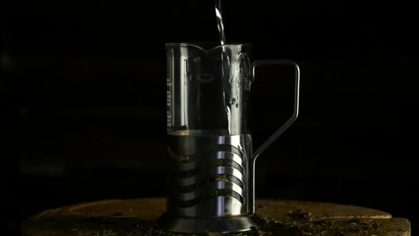 pour hot water leaves of tea in a glass teapot on a dark background. slow motion
