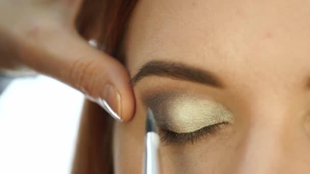 Close-up make-up artist hand, applying eyeshadow to womans eye using brush. slow motion