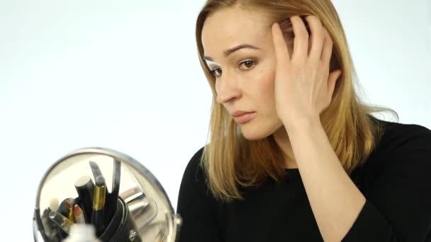 Mladá blondýnka stojí před zrcadlem doma a opravuje její vlasy. Zpomalený pohyb