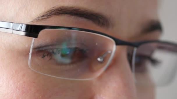 Detail Brownová očí v brýlích. Žena, pomocí chytrého telefonu. 4k
